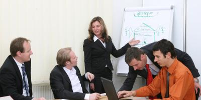 People in meeting with laptop on table in front of flipchart.